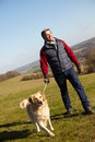 Man taking dog on walk in autumn countryside smiling Royalty Free Stock Photos