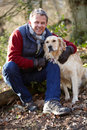 Man taking dog on walk through autumn woods smiling at camera Royalty Free Stock Photography