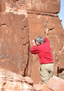 Man taking photograph of petroglyph panel photographer a photo along potash road near moab utah Stock Images