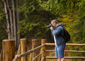 Man taking photos on the veranda in the forest Royalty Free Stock Photo