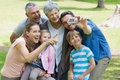 Man taking picture of extended family at park his cheerful the Royalty Free Stock Photo