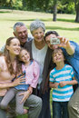 Man taking picture of extended family at park his cheerful the Stock Image