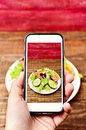 Man taking a picture of a salad with his smartphone Royalty Free Stock Photo