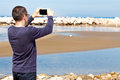 Man taking pictures with smartphone of beach the Royalty Free Stock Photos