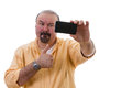 Man taking a selfie while giving a thumbs up middle aged with goatee standing posing self portrait on his mobile as he gives of Royalty Free Stock Photography