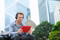 Man talking on tablet pc video chat conversation having in sitting outside using app g wireless device wearing headphones Stock Image