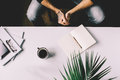 Man with tattoo holding  tablet on office desk table with , supplies, flower and cup of coffee. Top view Royalty Free Stock Photo