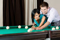 Man teaching girl to play billiards spending free time on gambling Stock Images