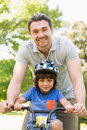 Man teaching his son to ride a bicycle portrait of smiling men Royalty Free Stock Images