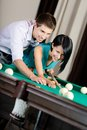 Man teaching woman to play billiards Royalty Free Stock Photography