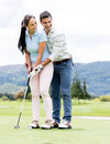 Man teaching woman to play golf women how at the course Stock Photography