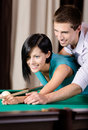 Man teaching young woman to play billiards Royalty Free Stock Photo