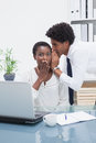 Man telling a business secret at his colleague in the office Stock Photography