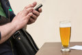 Man texting on his cell phone with a full glass of beer on the t Royalty Free Stock Photo
