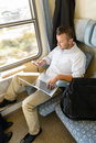 Man texting on phone holding laptop train Stock Image