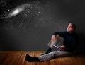 Man thinking a reclines on a wooden floor with an open journal and dreaming about the universe Stock Photography