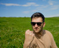 Man threatening with clenched fist sunglass on a green meadow Stock Photos