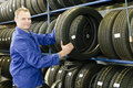 Man in the tire store with a tire Royalty Free Stock Photo