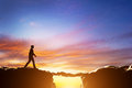 Man about to croos precipice between mountains over another man walking two serving as a bridge sunset business conceptual Stock Photo