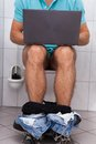 Man in toilet using laptop close up of a indoors Stock Image