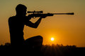 Man took aim with your sniper rifle young at sunset Royalty Free Stock Photography