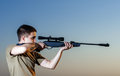 Man took aim with your sniper rifle young at sunset Royalty Free Stock Photos