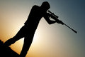Man took aim with your sniper rifle young at sunset Stock Photography