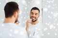 Man with toothbrush cleaning teeth at bathroom Royalty Free Stock Photo