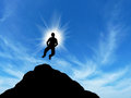 Man on top of the mountain reaches for the sun Stock Photography