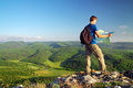 Man tourist in mountain read the map man on top of mountain tourism concept Stock Images