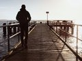 Man tourist at wooden sea pier. Cold windless morning with gradient sunlight. Smooth water Royalty Free Stock Photo