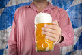 Man in traditional Bavarian shirt holds mug of beer Royalty Free Stock Photo