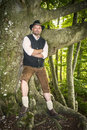 Man with traditional costume in forest bavarian is standing a Royalty Free Stock Photography