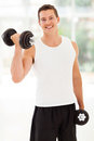 Man training dumbbells happy young with at the gym Stock Photo