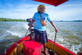 Man transporting people on the boat across the river Royalty Free Stock Photo