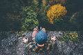 Man Traveler sitting on cliff bridge edge