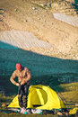 Man traveler with tent camping arranging hiking equipment in mountains traveling concept Royalty Free Stock Image