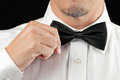 Man in tux straightens bowtie one hand close up of a a straightening his no jacket Royalty Free Stock Photo