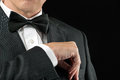 Man in tux tucks in pocket square close up of a a tucking his Royalty Free Stock Images