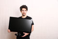 Man with a tv young hispanic holding flatscreen Royalty Free Stock Photo