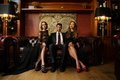 Man with two beautiful women handsome brunette wearing suit sitting on sofa Stock Photography
