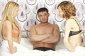 Man between two women in bed Stock Image