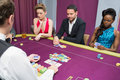 Man and two women playing poker waiting for the dealer at the casino Royalty Free Stock Photo