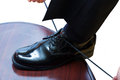 Man tying dress shoe detail of a black and pulling his laces Royalty Free Stock Photos