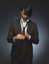 Man tying his necktie image of young mixed race fashion model in stylish suit getting dressed on black background Royalty Free Stock Photography