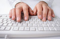 Man typing on a computer keyboard close up of the hands of in shirtsleeves white entering business data Royalty Free Stock Images