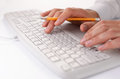 Man typing on a computer keyboard at work holding pencil in the fingers of one hand as he enters data close up view Royalty Free Stock Photo