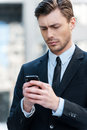 Man typing a message cheerful young holding mobile phone and looking at it Royalty Free Stock Photos