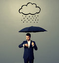 Man with umbrella looking at watch serious businessman black standing under drawing storm cloud and photo over grey background Stock Photography