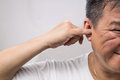 Man un hygienically cleaning ear using finger with ticklish expr expression Stock Photography